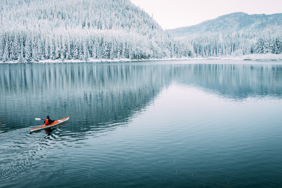 Stock photo of a red kayak in a blue lake in winter