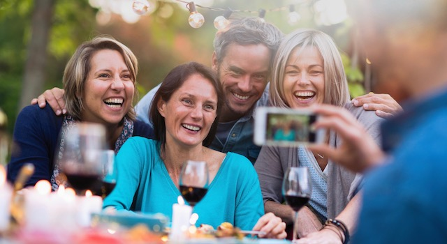 stock photography showing friends getting their photo taken at a dinner party